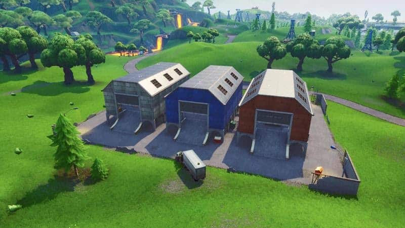 The Dusty Depot area in Fortntie, three long barns in an open field with some trees